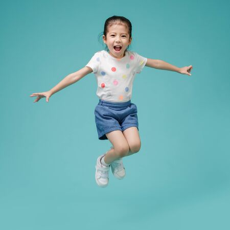 Playful energetic Asian little girl jumping in mid-air, empty space in studio shot isolated on colorful blue background Imagens