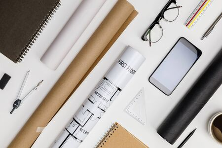 Creative flat lay of architects white table with roll blueprints, architectural project plan, engineering tools, office supplies and a cup of hot coffee,Workspace for designer concept Zdjęcie Seryjne