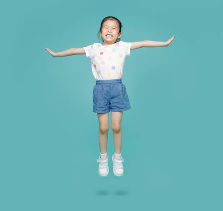 Excited Asian little girl jumping in mid-air, empty space in studio shot isolated on colorful blue background Stockfoto