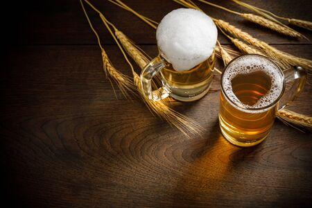 Vasos de cerveza ligera con trigo en la mesa de madera, espacio para copiar el texto Foto de archivo