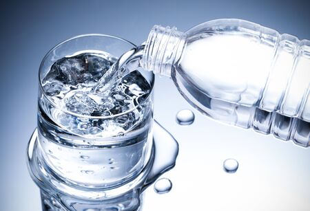 Pouring fresh pure water from bottle into a glass on the table with water drops, Healthcare and beauty hydration concept