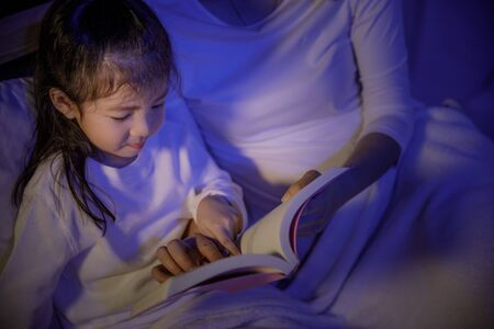 Mom reading a book with her daughter on bed in a dark bedroom at night before sleep, Parenthood and happy moments concept
