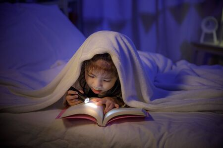 Child asian girl reading a book with flashlight under the blanket on bed in a dark bedroom at night before sleeping, Comfortable children at home concept
