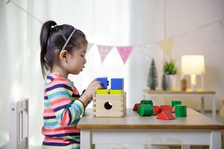 Kids creativity, Child little asian girl playing colorful building blocks on the desk in the class room at home, Educational concept for school Stock Photo