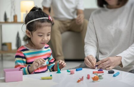 Mom with her daughter playing with a colorful toys modeling clay on the floor, at background daddy is sitting in a sofa in the living room, Happy asian family at home