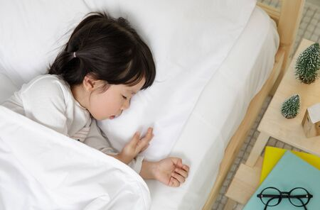 Child girl sleeping on the wooden bed in her bedroom, Happy asian child little girl sleep with blanket on the bed, christmas concept