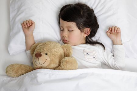 Child girl sleeping with teddy bear on the wooden bed in her bedroom, Happy asian child little girl with her teddy bear, family concept at home