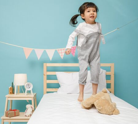 Child girl playing on the wooden bed in her bedroom, Happy asian child little girl jumping on the bed, happy family concept