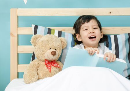 Child girl reading a book on the wooden bed in her bedroom, Happy asian child little girl with her teddy bear, learning concept at home