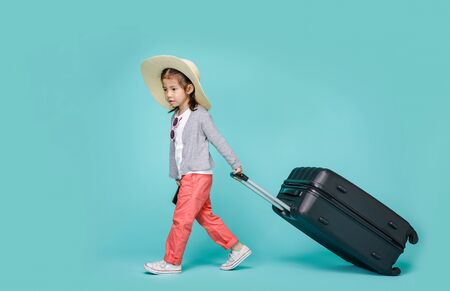 Asian little girl tourist woman with black luggage to travel on weekends, empty space in studio shot isolated on colorful blue background