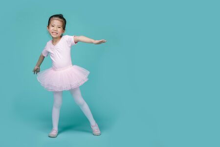 Beautiful smiling Asian little girl in a pink suit is dancing a ballet at school, empty space in studio shot isolated on colorful blue background