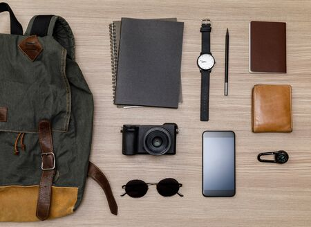 Top view mockup of Travelers accessories with passport, books of travel plan, wallet, camera, compass, backpack and mobile phone on brown wooden desk empty space, Travel concept background
