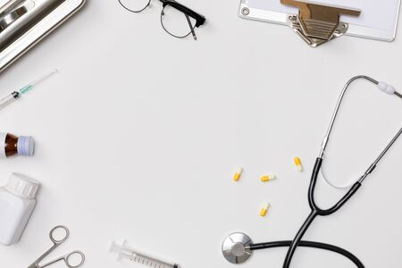 Creative flatlay of doctor medical equipment white table with stethoscope, medical documents, thermometer, syringe and pills, Health care concept, Top view with copy space, Isolated on white Reklamní fotografie - 130724954