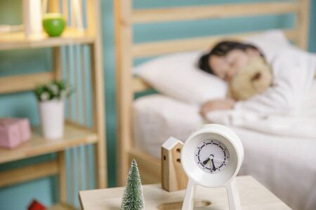 Child girl sleeping with alarm clock on the wooden bed in her bedroom, Happy asian child little girl and alarm clock wake up on the morning Stock Photo