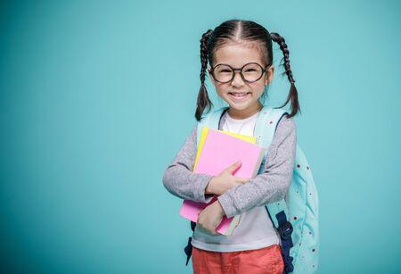 Piękna, uśmiechnięta Azjatycka dziewczynka w okularach i trzymaj książki z tornisterem jest z powrotem do szkoły, pustej przestrzeni w studio strzał na białym tle na kolorowym niebieskim tle, koncepcja edukacyjna dla szkoły Zdjęcie Seryjne