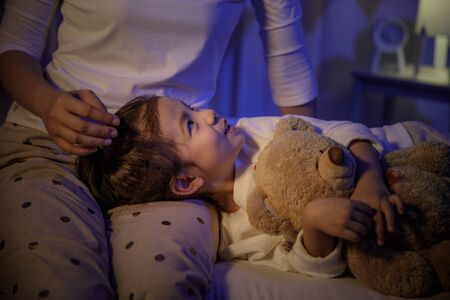 Mother stroking head of cute girl then sleeping on mom lap on bed in a dark bedroom at night, Child asian girl hug teddy bear, Comfortable children at home concept Stock Photo