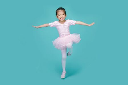 Beautiful smiling Asian little girl in a pink suit is dancing a ballet at school, empty space in studio shot isolated on colorful blue background Foto de archivo - 138998081