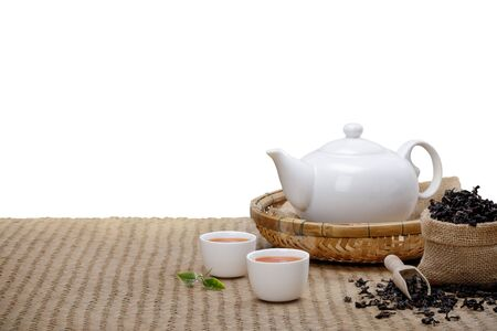 Warm cup of tea with teapot, green tea leaves and dried herbs on the bamboo mat at morning isolate white background with empty space, Organic product from the nature for healthy with traditional