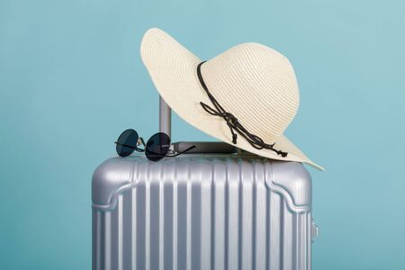 Travel Baggage with hat and sunglasses isolated on blue background with copy space, Travel concept background Zdjęcie Seryjne