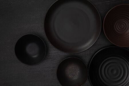 Group of empty blank black ceramic round bowls and plates on black stone blackground, Top view of traditional handcrafted kitchenware concept Banque d'images - 142147323