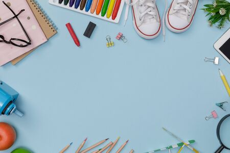 Creative flatlay of education blue table with student books, shoes, colorful crayon, eye glasses, empty space isolated on blue background, Concept of education and back to school