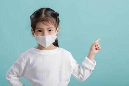 Petite fille asiatique portant un masque respiratoire pour protéger l'épidémie de coronavirus et pointant la main sur fond blanc, Nouveau virus Covid-19 du concept, Espace vide isolé sur fond bleu
