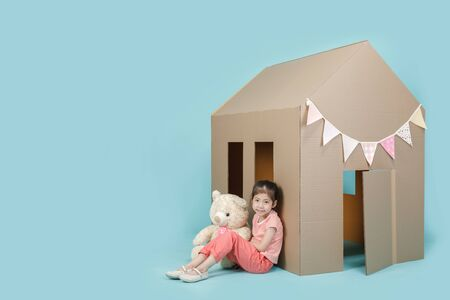 Asian little child girl playing with cardboard house with her teddy bear isolated on blue long banner with copy space for your text, Creative at home with family concept