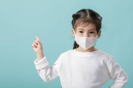 Asian little child girl wearing respirator mask to protect coronavirus outbreak and pointing hand to blank background, New virus Covid-19 from   concept, Empty space  on blue background