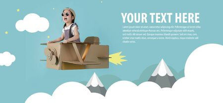 Asian little child girl playing with cardboard toy airplane handicraft over the clouds on blue sky long banner with copy space for your text, Creative with family and dreaming of flying concept Foto de archivo