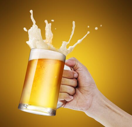Hand holding a mug of light beer toasting with bubble froth splash in golden background with copy space