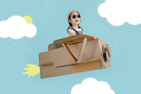 Asian little child girl playing with cardboard toy airplane handicraft over the clouds, Creative at home and dreams of flight concept