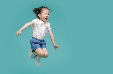 Excited Asian little girl jumping in mid-air, empty space in studio shot isolated on colorful blue background 免版税图像