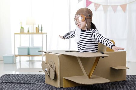 Asian little child girl playing with cardboard toy airplane handicraft in living room with copy space for your text, Creative at home and dreams of flight concept