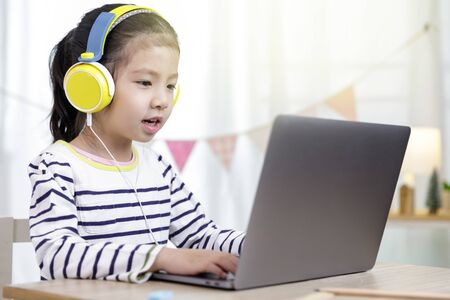 Asian little child girl learning at home with laptop computer using meeting online app, Quarantine isolation during the Coronavirus (COVID-19) health care, online education concept Stock Photo