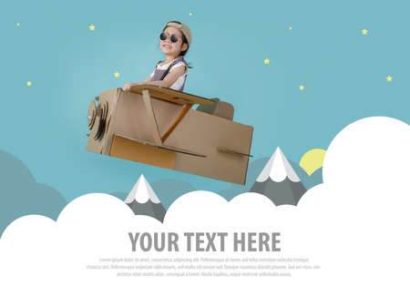 Asian little child girl playing with cardboard toy airplane handicraft over the clouds with copy space for your text, Creative at home and dreams of flight concept