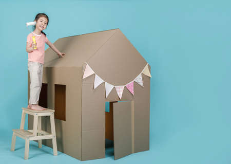 Asian little child girl painting her cardboard house isolated on blue long banner with copy space for your text, Creative at home with family concept