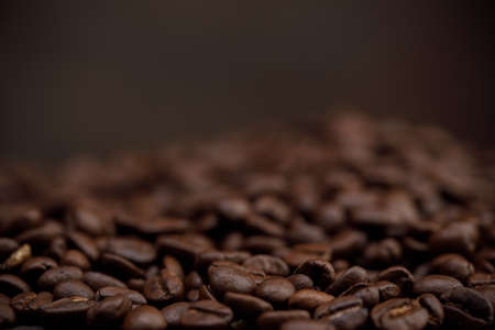 The hot of brown roasted coffee beans on brown background with copyspace, Healthy products by organic natural ingredients concept