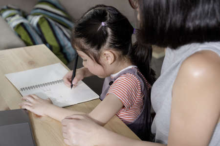 Businesswoman mother woman with a child girl working on the desk in the home, Working from home lifestyle concept, Quarantine isolation during the Coronavirus (COVID-19) health crisis