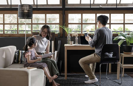 Working from home lifestyle father using smartphone on the desk and child girl learning with her mother on sofa in the living room, Quarantine isolation during the Coronavirus (COVID-19) health crisis 免版税图像