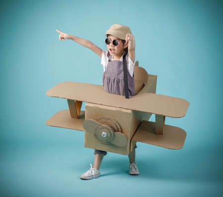 Asian little child girl playing with cardboard toy airplane handicraft isolated on blue background, Creative with family and dreaming of flying concept 免版税图像