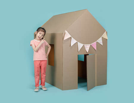 Asian little child girl playing with cardboard house isolated on blue long banner, Creative at home with family concept