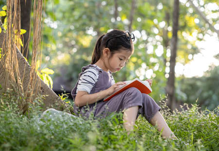 A pretty little Asian girl reading a book under the big tree.