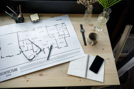 Top view workspace mockup of architectural project with architectural project plan, engineering tools, office supplies and hot coffee cup on wooden desk empty space 免版税图像