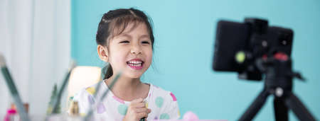 Happy little Asian girl beauty blogger live video streaming and teaching to use cosmetic make up for kids.