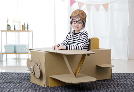 Asian little child girl playing with cardboard toy airplane handicraft in living room with copy space for your text, Creative at home and dreams of flight concept 免版税图像