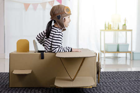 Asian little child girl playing with cardboard toy airplane handicraft isolated in home with copy space for your text, Creative with family and dreaming of flying concept