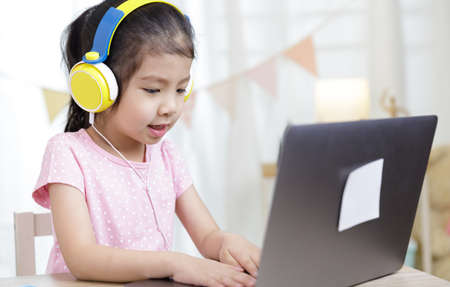 Asian little child girl learning at home wear headphone talk video calling with laptop meeting online app, Quarantine isolation during the Coronavirus (COVID-19) health care, online education concept