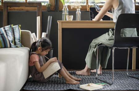 Working from home lifestyle mom using laptop on the desk and her child girl write a book at sofa in the living room, Quarantine isolation during the Coronavirus (COVID-19) health crisis