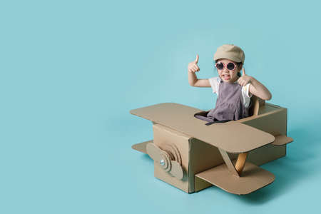 Asian little child girl playing with cardboard toy airplane handicraft isolated on blue long banner with copy space for your text, Creative at home and dreams of flight concept