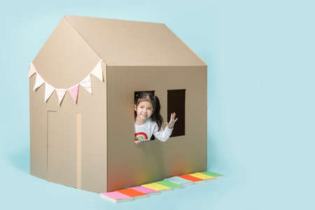 Asian little child girl playing with cardboard house isolated on blue long banner with copy space for your text, Creative at home with family concept